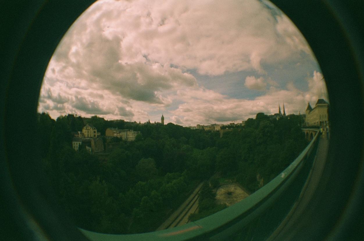 Blick auf das Petrus-Tal in Luxemburg-Stadt. Im Vordergrund ein grünes Geländer, ein grünes Tal, durch das ein kleines Rinsal fließt, im Hintergrund einige Gebäude von Luxemburg-Stadt