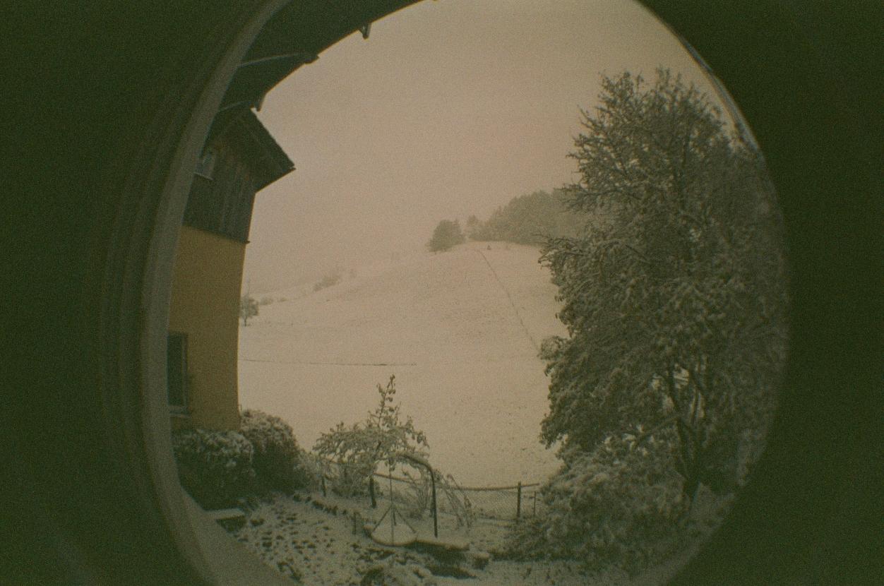 Fischaugenfoto aus einem Fenster heraus auf einen verschneiten Hügel. Am linken Bildrand ist ein Haus zu erkennen, am rechten ein Baum.