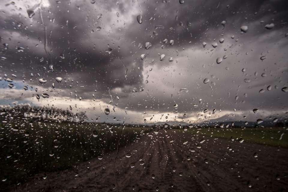 Foto von grauen Wolken über einem matschigen braunen Feld. Das Foto ist durch eine Fensterscheibe fotografiert, auf dem Regentropfen zu sehen sind Photo by SplitShire