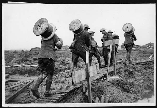 Signallers carrying large rolls of telegraph wire. The rolls look like large cotton reels, with a stick attached for carrying. The men are walking over a muddy and exposed area. Duckboards have been laid on the ground to make it easier underfoot. All of the men are in uniform and wearing steel helmets. Three men stand off to the side talking. To the right of the pathway the ground looks water-logged and dangerous.
