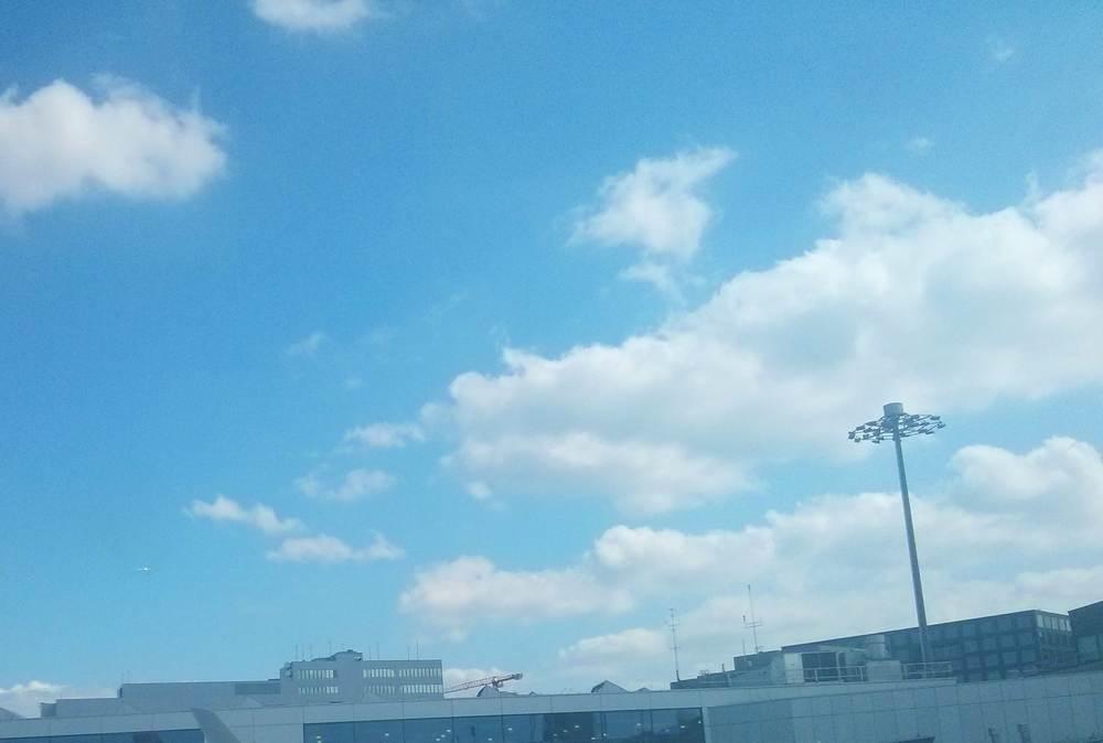 Foto des Züricher Flughafens, vor allem blauer Himmel mit Wolken, am unteren Rand sind Flughafengebäude zu sehen, wir sehen auch ein kleines am Horizont verschwindendes Flugzeug
