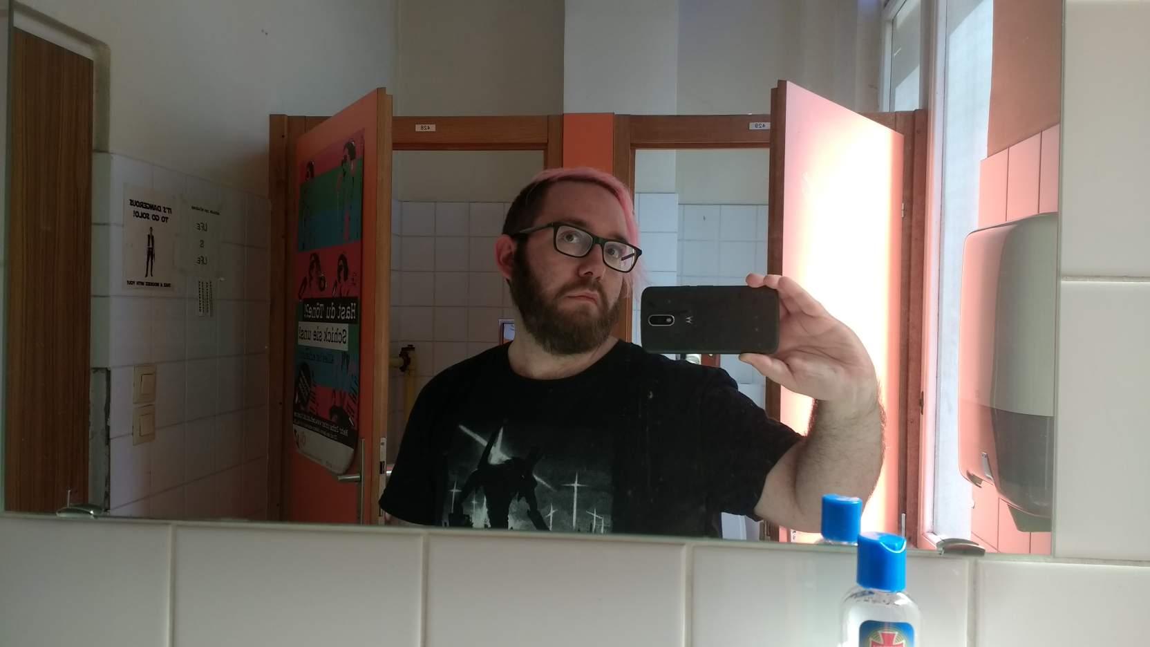 Joël steht auf einem Klo und macht ein Selfie, skeptischer Blick