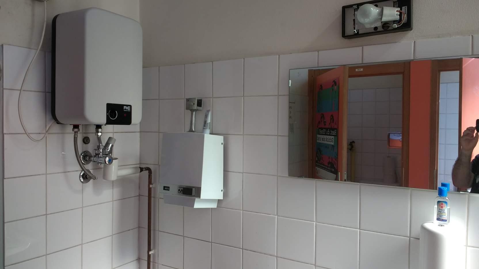 Das Klo der ÖH-Bundesvertretung. Zu sehen sit vor allem ein Wasserboiler, ein Spiegel in dem eine Hand mit Handy zu sehen ist, im Hintergrund zwei offene orange Klotüren