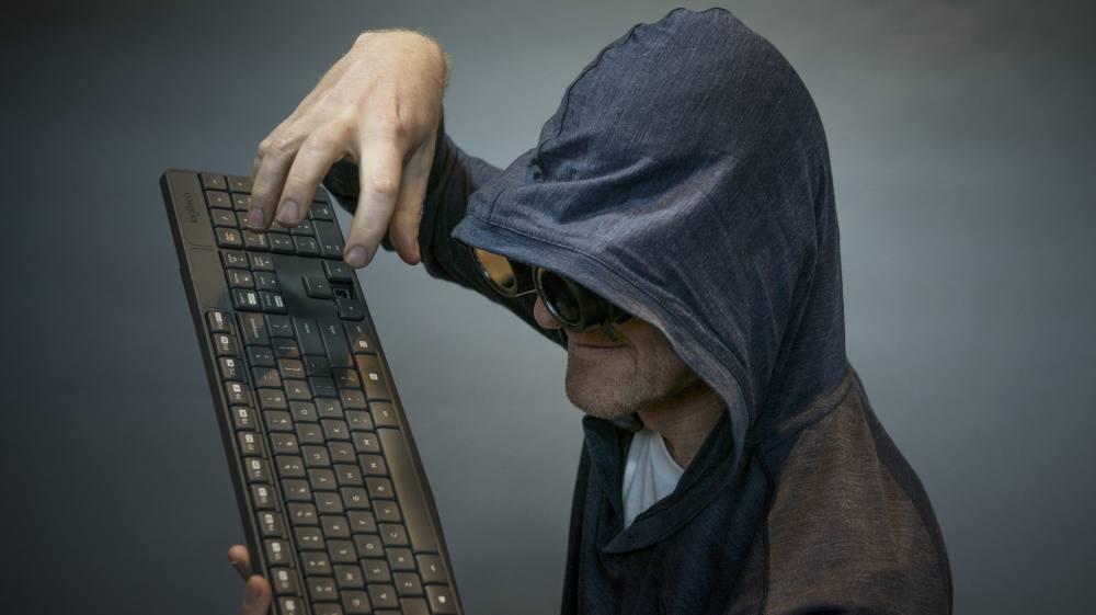 Ein ironisch übertriebenes Stock-Foto eines Hackers. Ein Mann hält eine schwarze Tastatur. Er trägt einen dunklen Kaputzenpullover und ein Nachtsichtgerät, von seinem Gesicht ist nur sein Kinn zu erkennen.