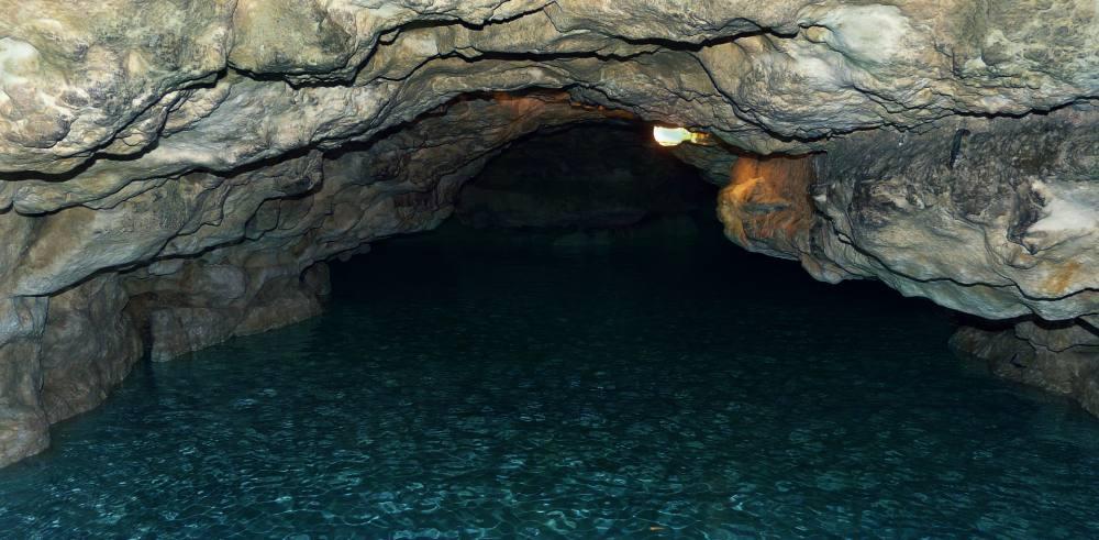 Höhle, auf deren Grund blaues Wasser zu sehen ist.