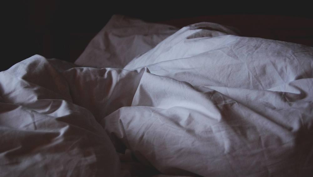 Ein Bett im Dunkeln, es sind weiße Laken sichtbar.