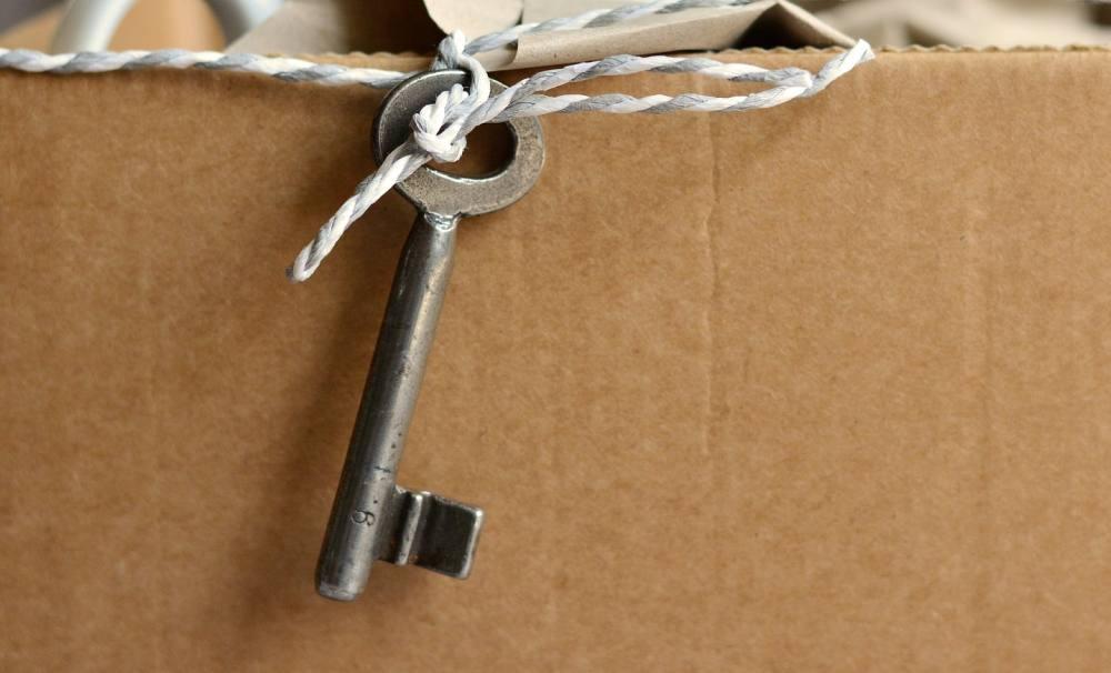 Ein alter Schlüssel an einer Schnur vor einem Karton.