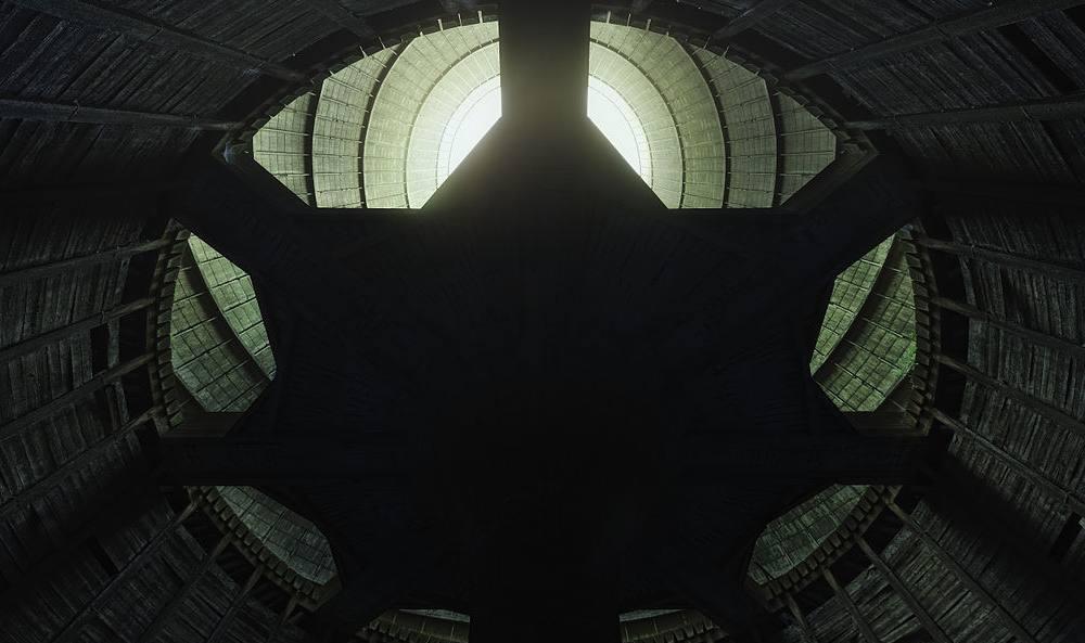 Blick von unten nach oben aus einem Betonschacht. Einige Meter über dem Blickpunkt ist eine sternenförmige Plattform.