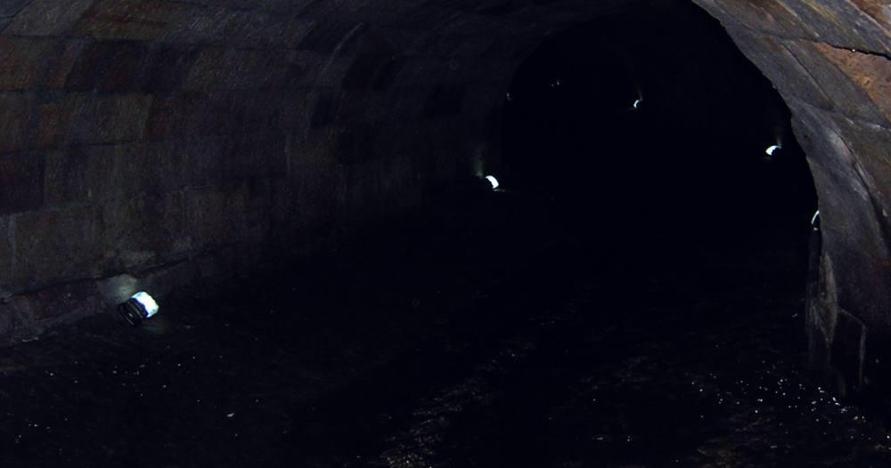 Ein Tunnel, spärlich beleuchtet, der Boden ist mit Wasser bedeckt.