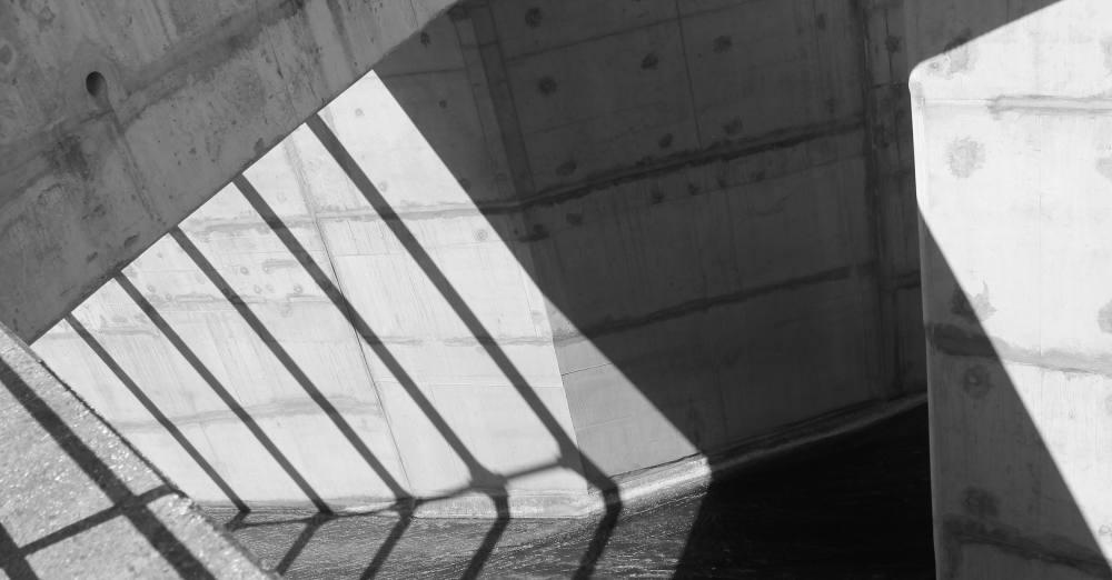 schwarz-weiß Foto von Betonstrukturen. Unten im Bild ist Wasser zu erkennen.
