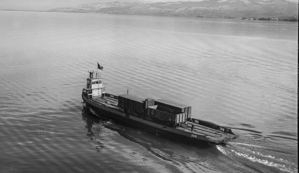 Ein Schiff, auf dem drei Eisenbahnwaggons stehen, fährt über den Bodensee.