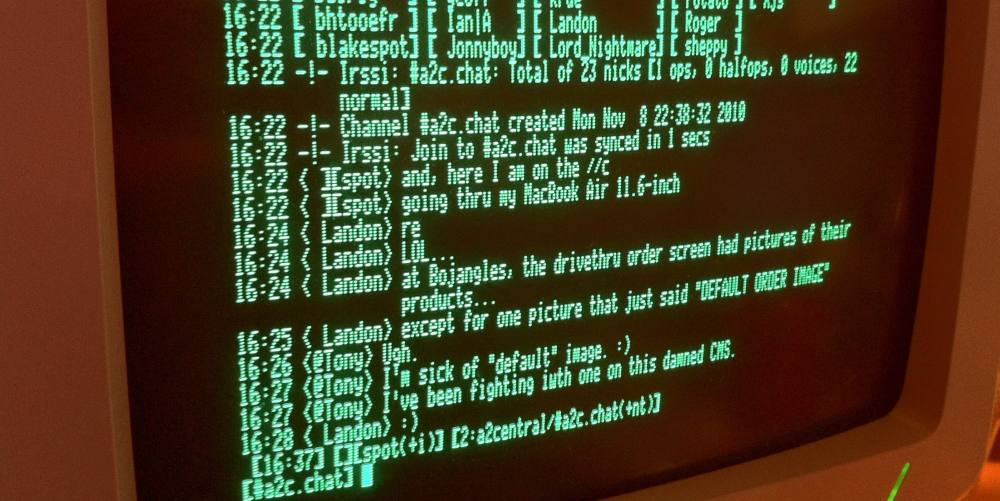 Foto eines alten Computers, auf dem ein IRC-Chat läuft. Die Schrift ist grün auf schwarzem Grund.