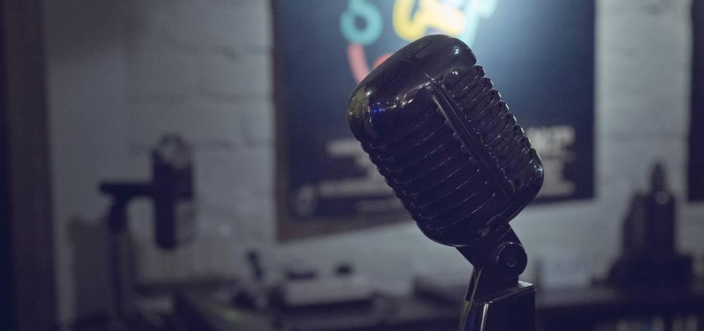 Ein auf alt getrimmtes Mikrofon vor einer weißen Wand, an dem ein buntes Poster hängt.
