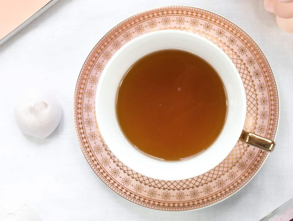 Eine filigrante Tasse mit orangem Muster und  Tee in der gleichen Farbe.
