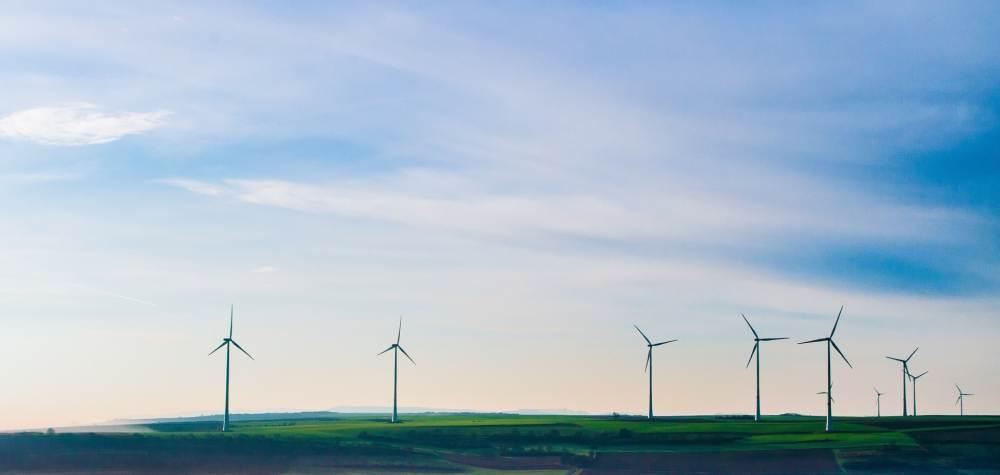 Eine grüne Landschaft mit einigen Windkraftanlagen drauf. Darüber blauer Himmel mit vielen freundlichen weißen Wolken.