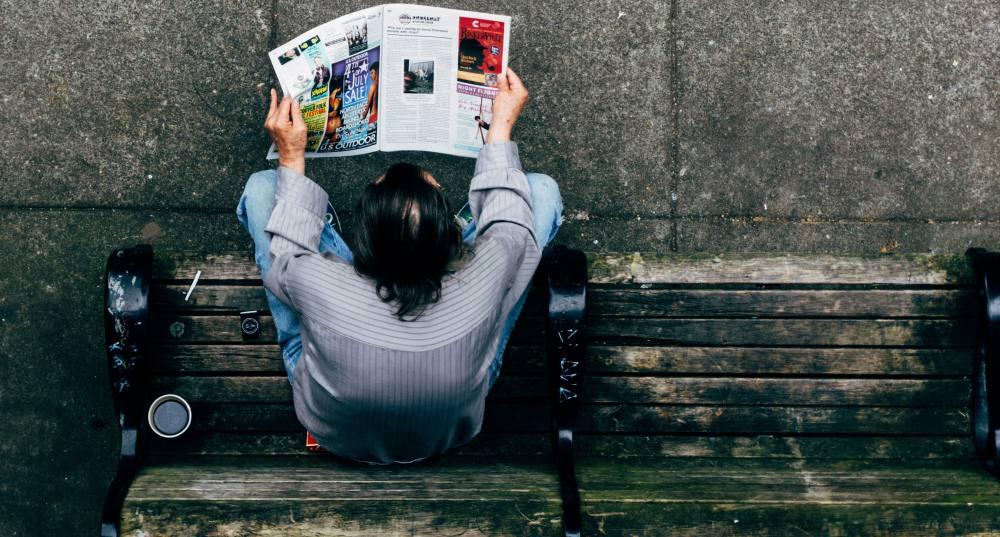 Foto von oben. Wir sehen einen Mann auf einer Parkbank, der eine Zeitung liest. Neben ihm sthet eine Tasse Kaffee.