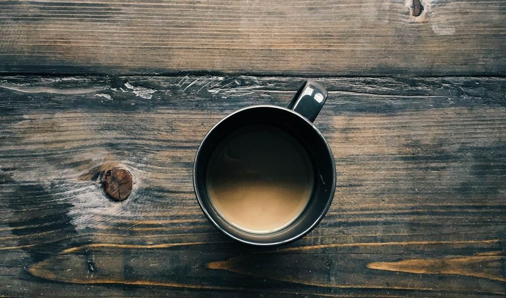 Eine Tasse Kaffee auf einem dunklen Holztisch