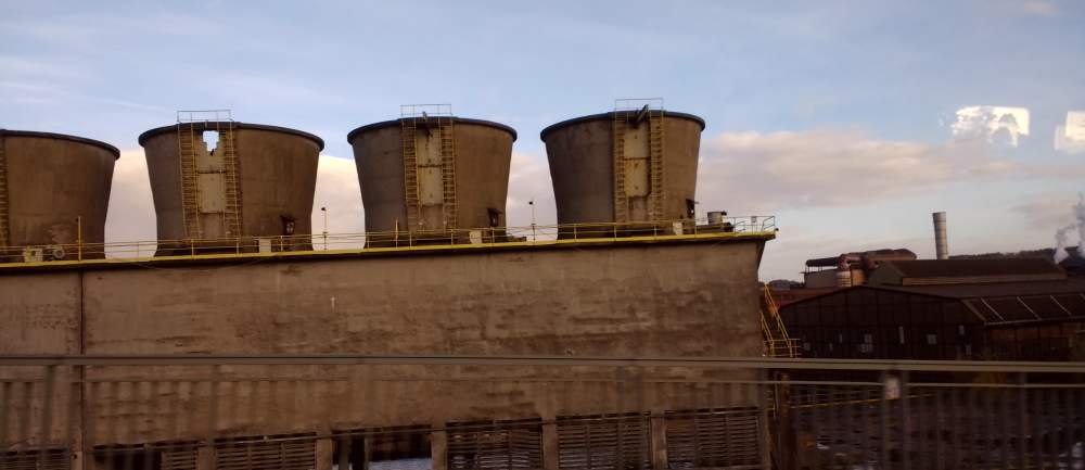 Vier Kühltürme und eine Halle eines Stahlwerkes. Im Vordergrund ist ein Geländer zu sehen, im Hintergrund zartrosa Himmel mit Wolken. Das Foto ist aus einem Bus aufgenommen, die Spiegelung der Scheibe ist zu sehen.