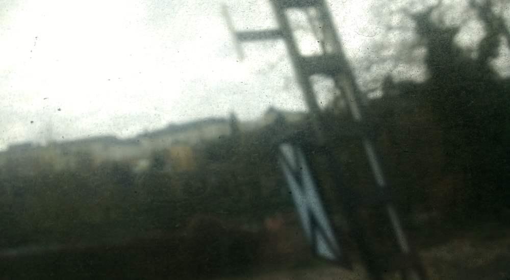 Verschwommenes Foto aus dem Zugfenster. EIne Stadt ist im Hintergrund zu erahnen, im Fordergrund ein Metalpfosten mit Eisenbahnsignal. Scharf ist aber nicht der Blick aus dem Fenster, sondern der Schmutz auf dem sehr schmutzigen Zugfenster.