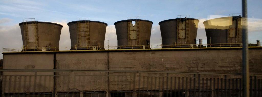 Fünf Kühltürme eines Stahlwerkes nebeneinander. Nur die Spitzen sind zu sehen, davor steht eine graue Wand, davor ist ein Geländer zu sehen. Im Hintergrund blauer Himmel und einige Wolken.