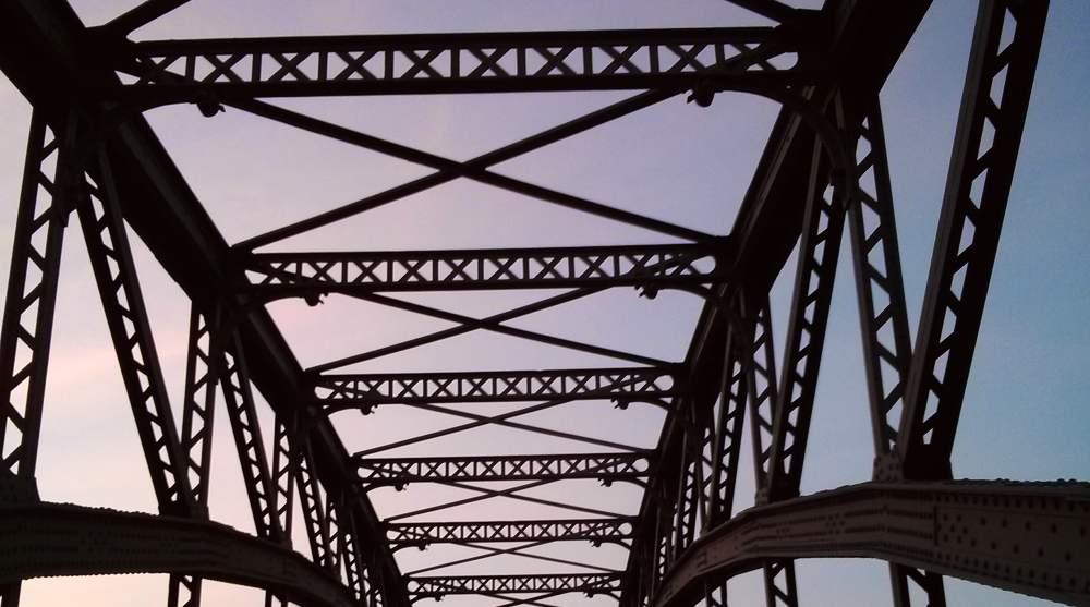 Eine Stahlbrücke vor leicht rosa Sonnenuntergangshimmel
