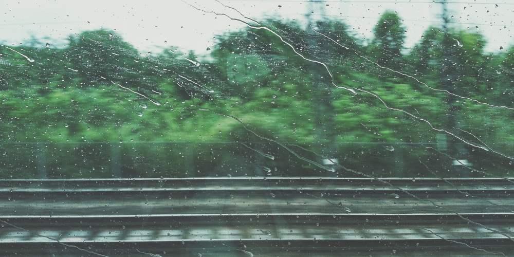 Blick aus einem Zugfenster, auf dem Regentropfen zu sehen sind.