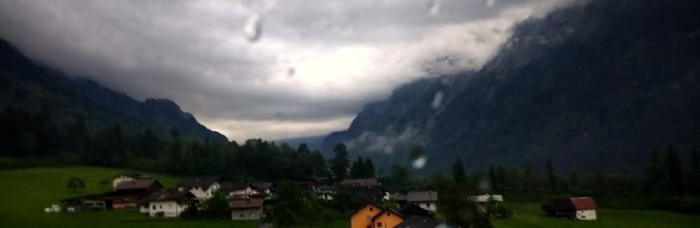 Ein Bergtal mit einigen bunten Häusern und einem sehr bedrohlichen, düstern Himmel.