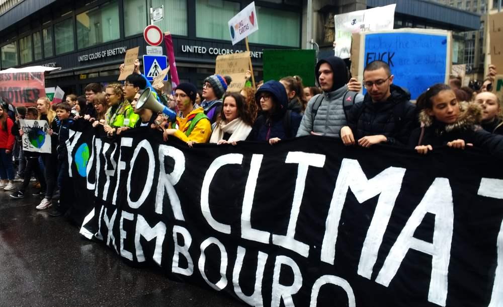 """Klimademonstration in Luxemburg. Die Spitze der Demo ist zu sehen, junge Menschen tragen ein Transparent mit der Aufschrift """"Youth for Climate Luxembourg"""". Im Hintergrund sind viele Schilder zu sehen."""