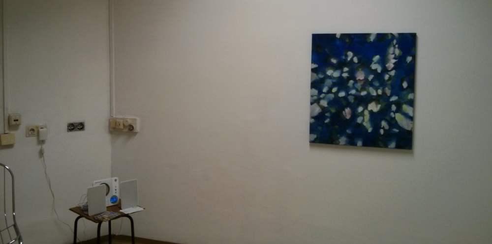 Eine weiße Wand, an der ein einziges buntes Bild hängt. Daneben viele Steckdosen, auf einem Hocker steht eine Stereoanlage.