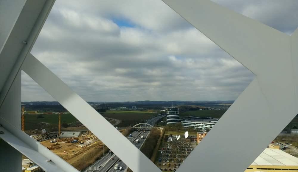 Blick auf eine Autobahn, einen Parkplatz und eine Baustelle von einem Turm herab. Am Horizont und am Himmel sind viele weiße Wolken zu sehen.