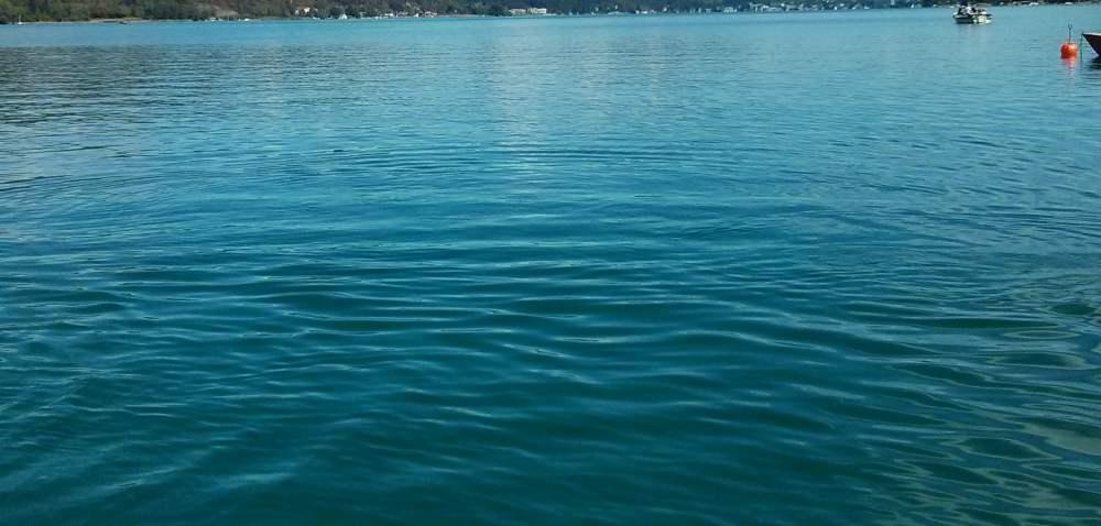ein Badesee. Es ist nur ein schmaler Streifen Horizont zu sehen, sonst nur Wasser, im Hintergrund ein Boot und eine Boje