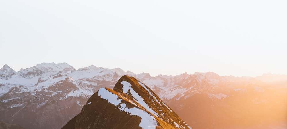 Die Spitze eines Berges, im Hintergrund weitere schneebedeckte Gipfel