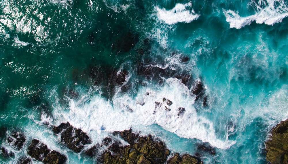 Luftbildaufnahme von Wellen, die gegen Felsen schlagen