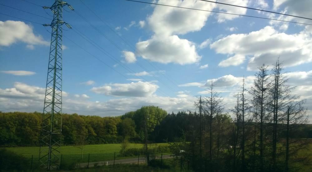 Strommast, Stromleitung, ein Wald, eine Straße, darüber ein großes Stück Himmel mit vielen weißen Wolken