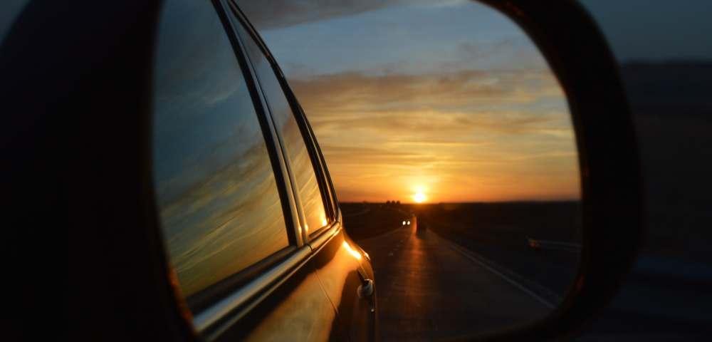 ein sonnenuntergang im rückspiegel eines autos
