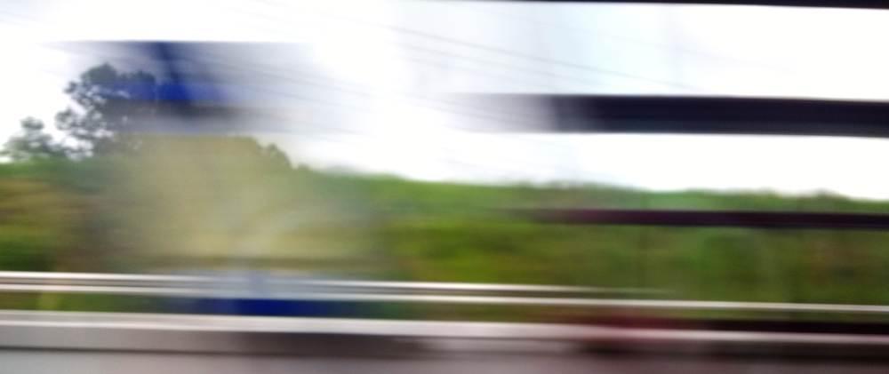 Bahnsteig, aus dem fahrenden Zug aufgenommen. Alles vers