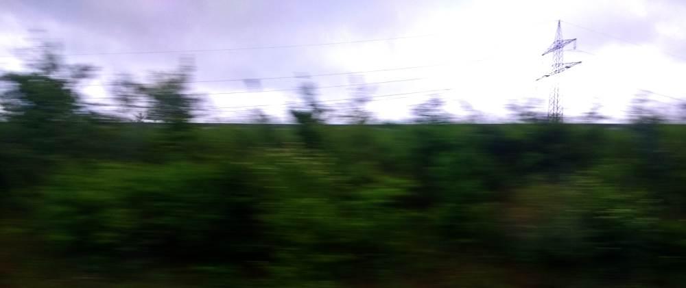 Ein verschwommenes Bild einer Landschaft, grün mit düsterem Himmel. In der Ferne ist ein Hochspannungsmast zu sehen.