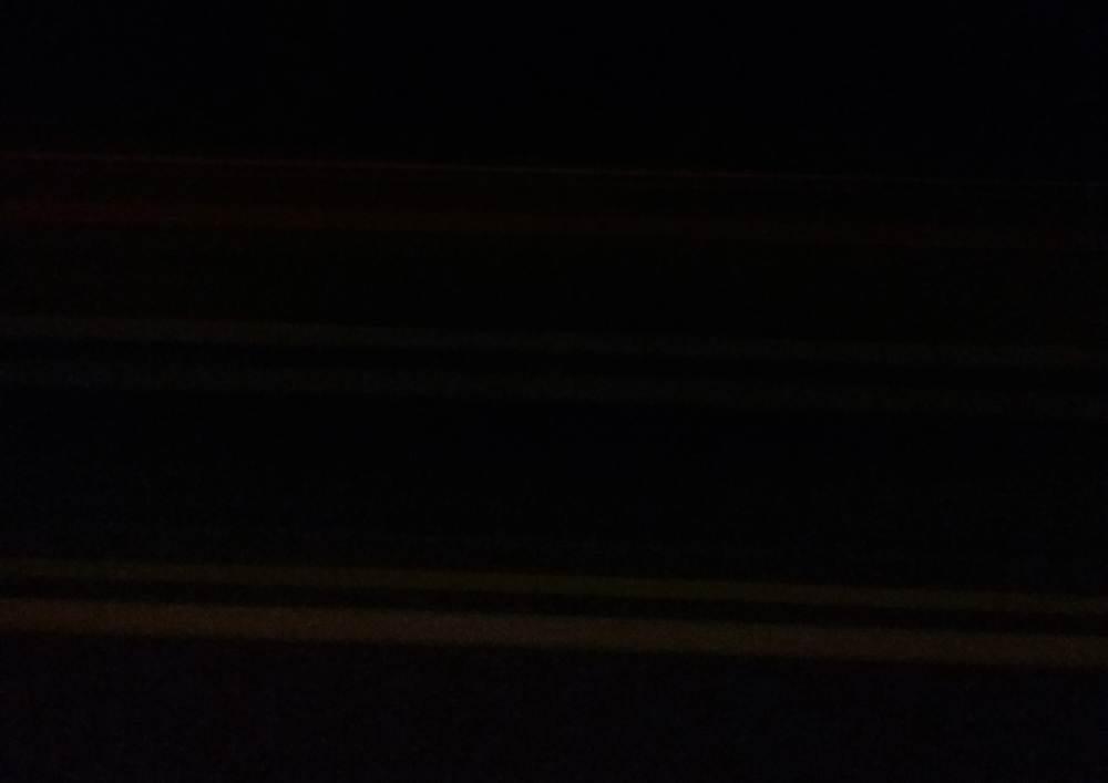 eine Autobahn, zu sehen ist eine Leitplanke und die Fahrbahnmarkierung in der Nacht, der Rest ist Dunkel und Bewegungsunschärfe.