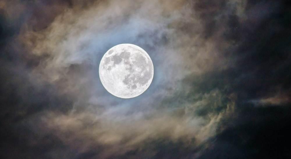 Der Mond hinter leichten Wolkenfetzen